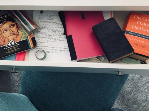 Desk drawer with the essentials: dictionaries, writing notebook, colored pencils, and positive manuscript critique from an editor